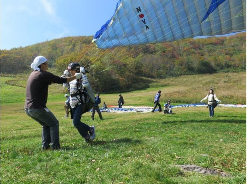 Run by himself, put air in the paraglider and raise it above the head